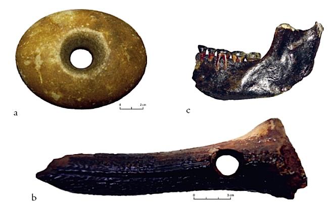 Sélection d'artefacts préhistoriques du Brown Bank. a) hache de pierre polie; b) bois de cerf perforés; c) mâchoire humaine.